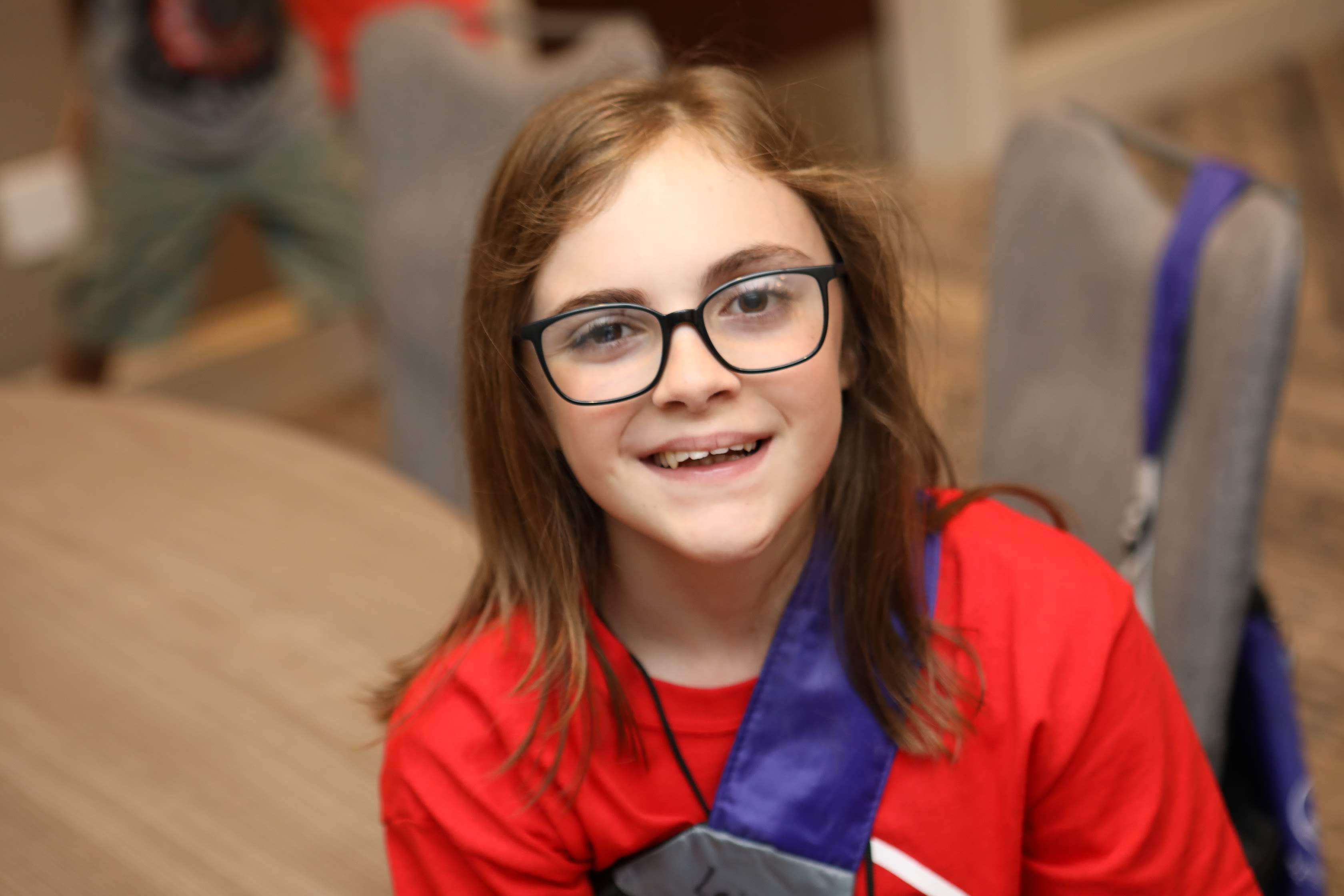 young girl with medium brown hair and glasses with VEDS smiling at the camera