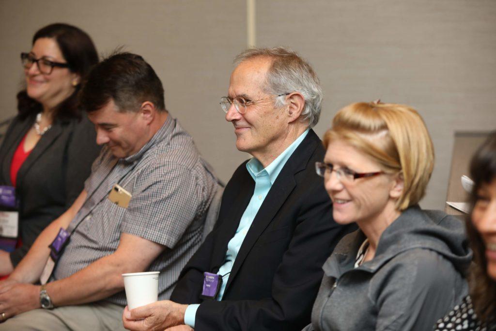 Four people sitting left to right: woman, dark hair, glasses, gray blazer, man, short brown hair, gray shirt, older man, black blazer, smiling, woman, blonde, gray sweater, smiling.