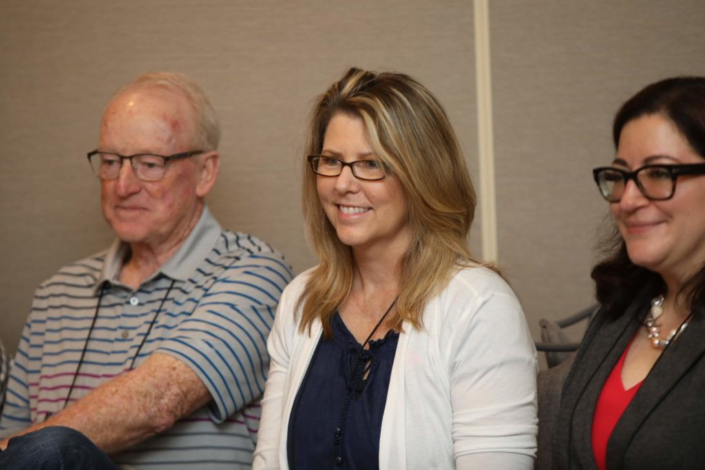 woman with blonde hair and white shirt smiling in between an older gentleman on the left side and a woman with dark hair and glasses on the right