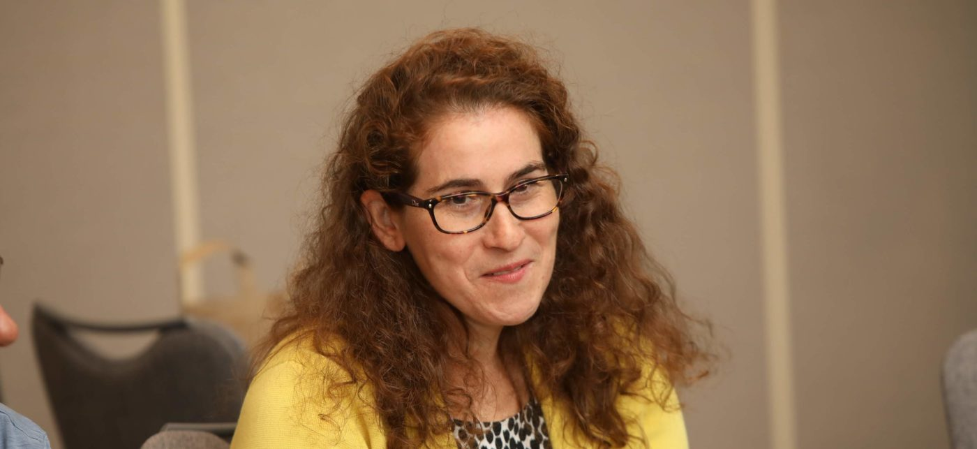 A woman with long curly hair wearing yellow sweater in a conference room-
