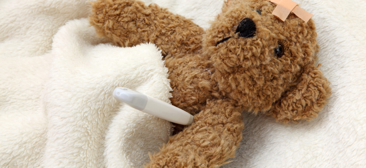 teddy bear with bandaid on head and thermometer under armpit