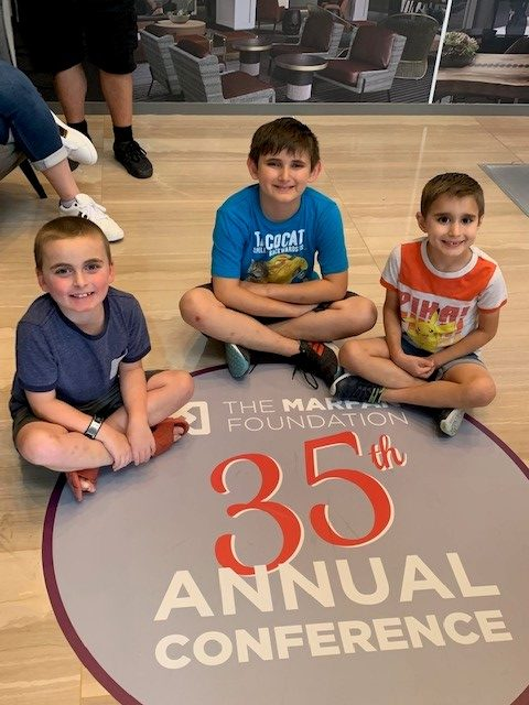 Three young boys with VEDS sitting cross legged on the floor smiling next to a floor sticker that says The Marfan Foundation 35th Annual Conference