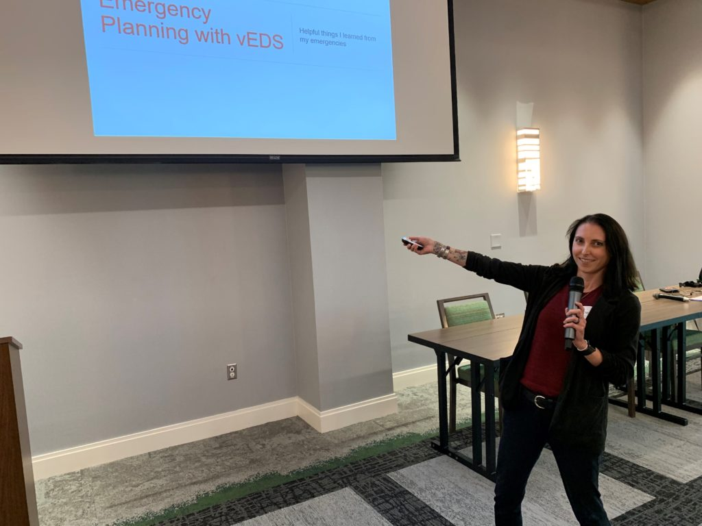 Woman with black hair and red shirt and black jacket pointing at powerpoint presentation titled Emergency Planning with vEDS