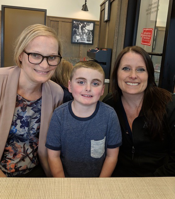 blonde woman with glasses, young boy, woman with brown hair smiling at camera. All have vEDS