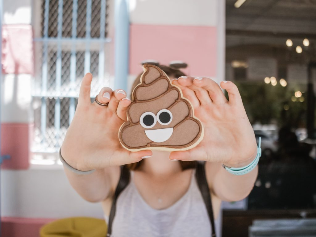 woman holding poop emoji to the camera