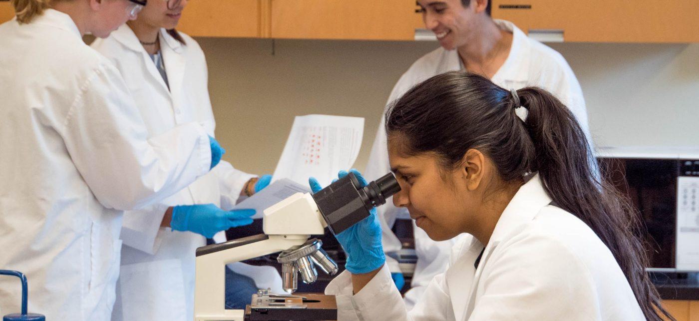 woman in labcoat looking in microscope
