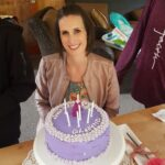 woman with short dark brown hair smiling in front of a purple birthday cake